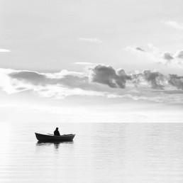 Mies istuu järvellä veneessä auringonlaskussa